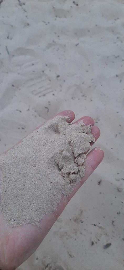 речной песок в руке